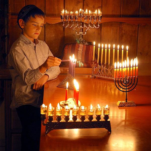 A young boy lights a chanukah menorah in this professional photograph of Israel by Yehoshua Halevi.