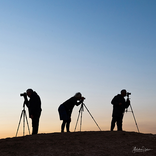 Three photographers with cameras and tripods stand in silhouette on a hilltop during a Judean Desert sunrise