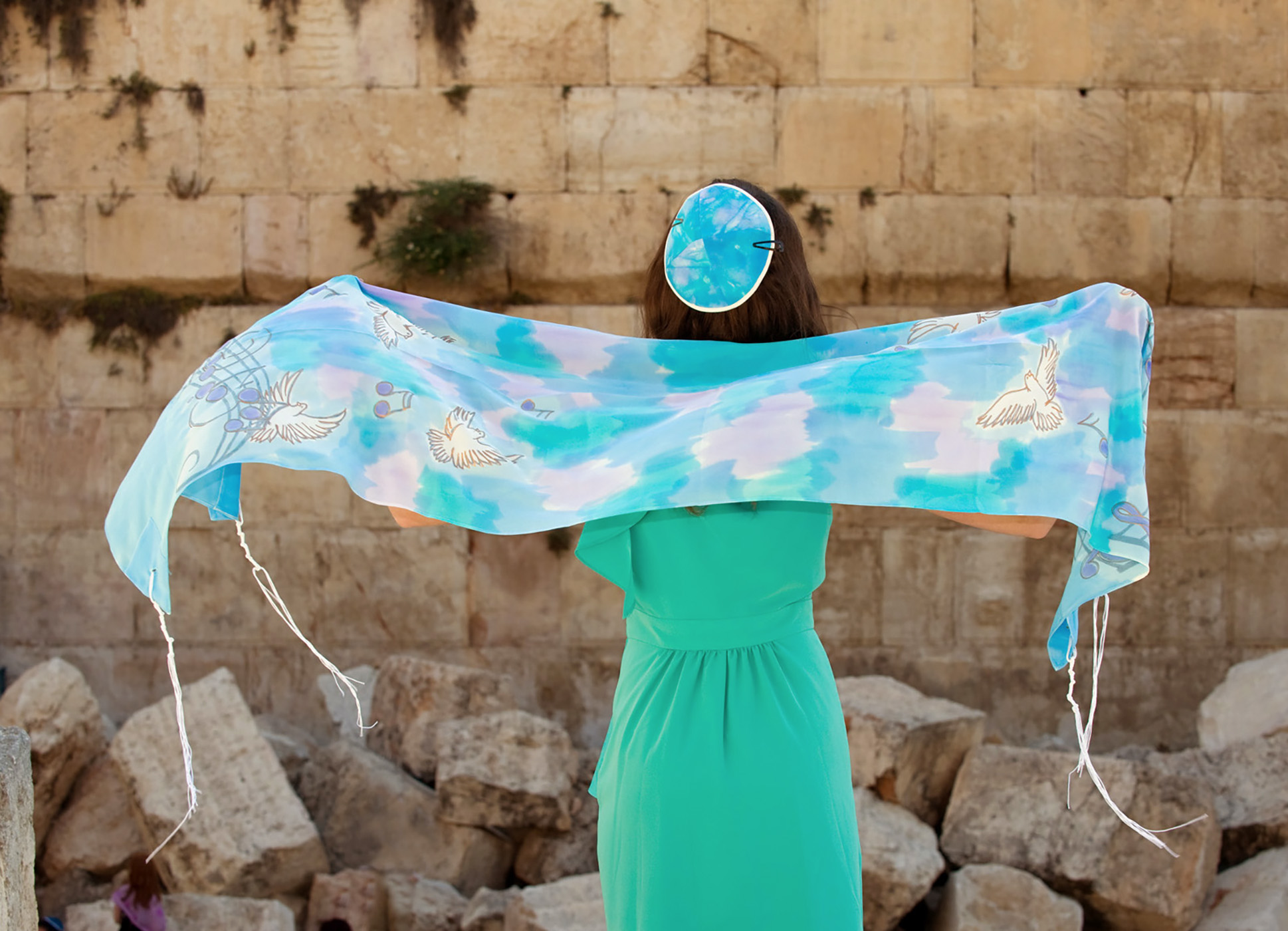 Bat mitzvah girl holds a prayer shawl by the Western Wall in Jerusalem.