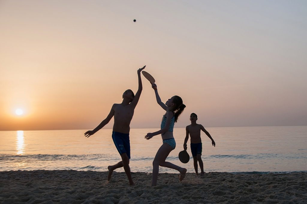 In this classic professional photograph of Israel, children play matkot, a popular paddle ball game on a beach at sunset.
