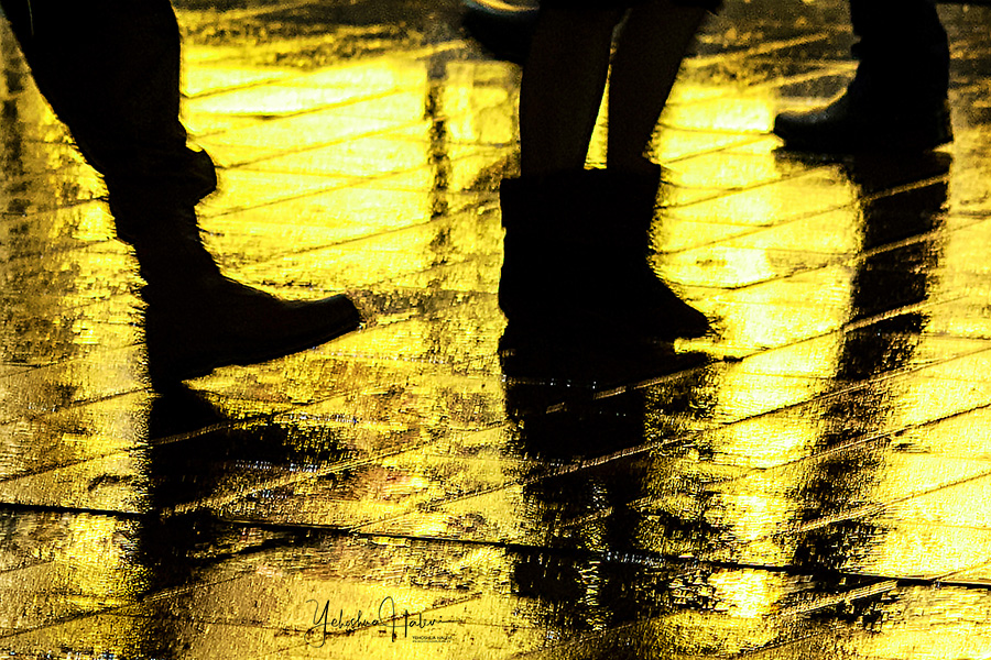 Silhouette of feet on a wet, colorful sidewalk in Jerusalem at night symbolic of our need to pay attention to climate change